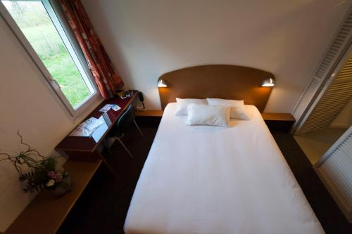 A bed or beds in a room at Quick Palace Pau Zénith