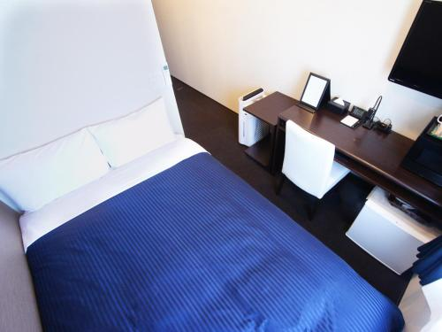A bed or beds in a room at Hotel Livemax Yokohama Motomachi Ekimae