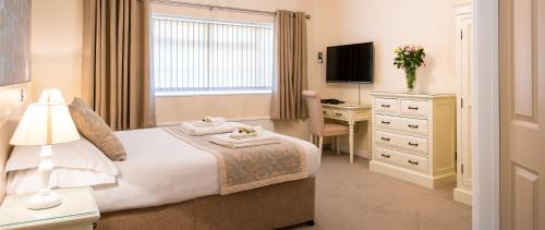 A bed or beds in a room at Maison Gorey Hotel