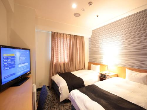 A bed or beds in a room at APA Hotel Yamaguchi Hofu