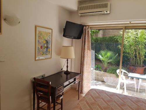 A television and/or entertainment center at Hotel La Cle Du Sud