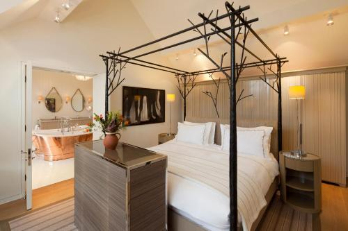 A bed or beds in a room at Coworth Park - Dorchester Collection