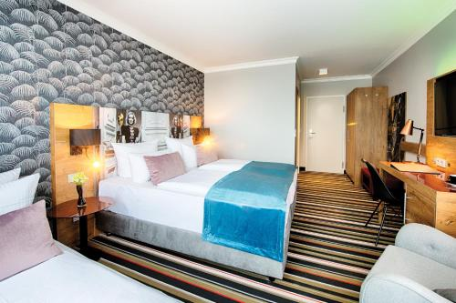 A bed or beds in a room at Leonardo Boutique Hotel Berlin City South