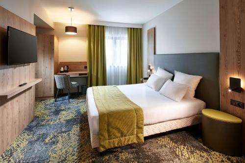 A bed or beds in a room at Hôtel Turenne