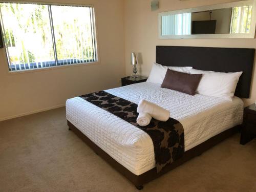A bed or beds in a room at Grange Resort Hervey Bay