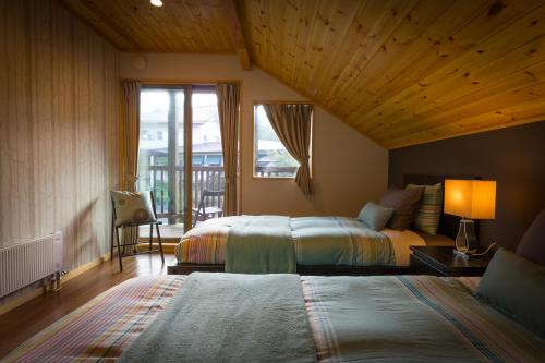 A bed or beds in a room at Hakuba Powder Cottage