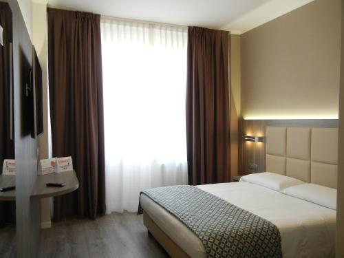 A bed or beds in a room at Delle Nazioni Milan Hotel