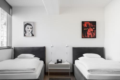 A bed or beds in a room at Augarten Art Hotel