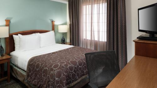 A bed or beds in a room at Staybridge Suites Jackson, an IHG Hotel
