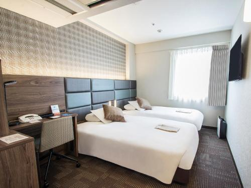 A bed or beds in a room at Hearton Hotel Shinsaibashi