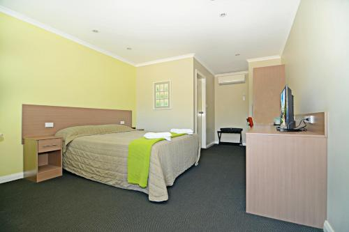 A bed or beds in a room at Heritage Hotel