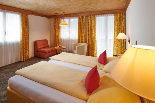 A bed or beds in a room at Hotel Central Wolter - Grindelwald