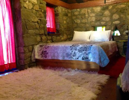 A bed or beds in a room at Marina's Stone Cottage