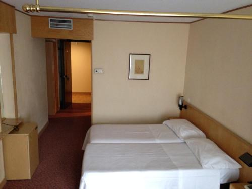 A bed or beds in a room at Hotel Les Jumeaux Courmayeur