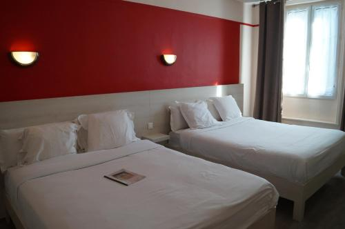 A bed or beds in a room at Brit Hotel Du Dauphin L'Aigle
