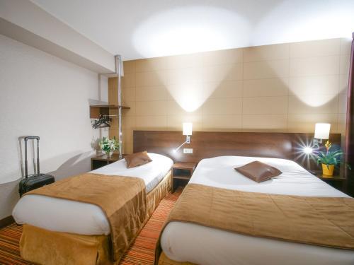 A bed or beds in a room at Hôtel Inn Design Resto Novo Alençon