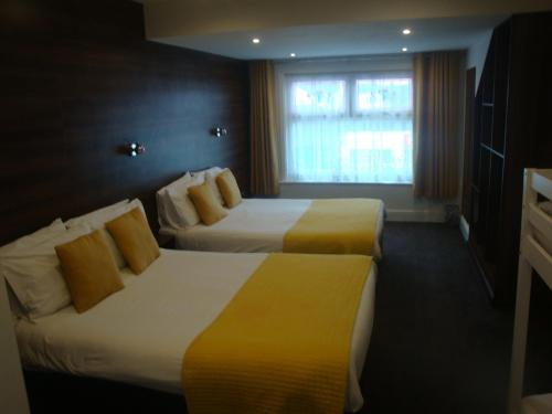 A bed or beds in a room at The Sandhurst Hotel