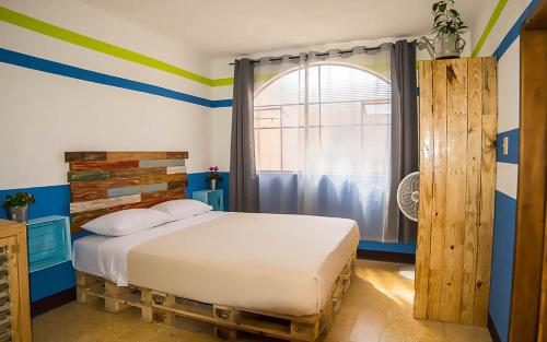 A bed or beds in a room at The Purpose Hostel