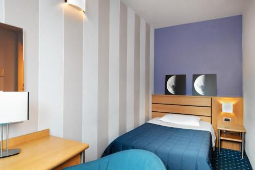 A bed or beds in a room at Garda Hotel