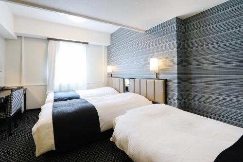 A bed or beds in a room at APA Hotel Sapporo Susukino Ekimae