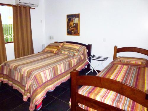 A bed or beds in a room at Pousada Ancoradouro