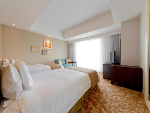 A bed or beds in a room at Hotel Universal Port