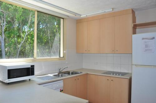 A kitchen or kitchenette at 32/15 Rainbow Shores - Unit overlooking bushland with shared swimming pool, spa and tennis court