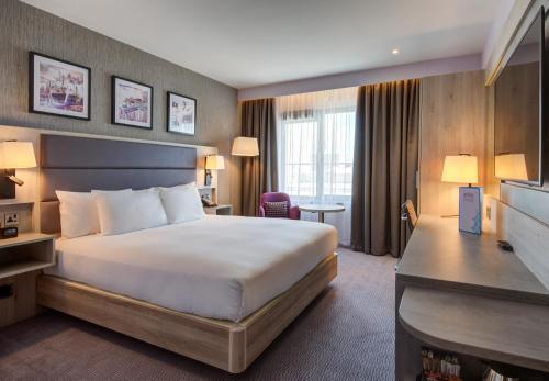 A bed or beds in a room at Hilton Garden Inn Dublin Custom House