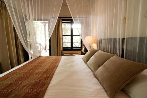 A bed or beds in a room at Hotel Jungle Lodge Tikal