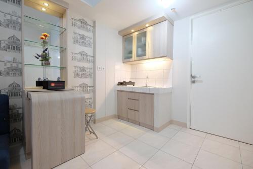 A kitchen or kitchenette at 3BR near Sumarecon Mall Bekasi at The Springlake Apartment by Travelio