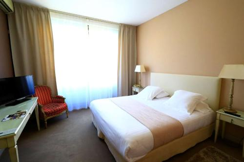 A bed or beds in a room at Best Western Le Renoir