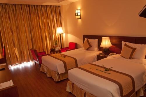 A bed or beds in a room at DLGL - Dung Quat Hotel