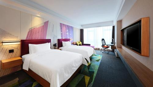 A bed or beds in a room at Hampton by Hilton Guangzhou Zhujiang New Town