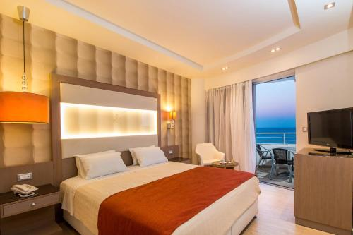 A bed or beds in a room at Pegasos Deluxe Beach Hotel