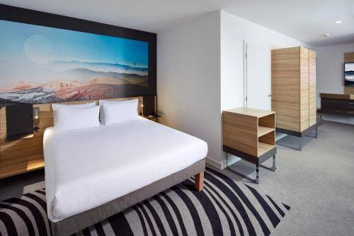 A bed or beds in a room at Novotel Suites Colmar Centre