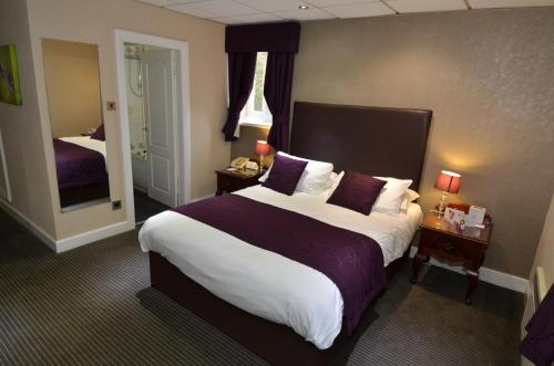 A bed or beds in a room at Best Western Chorley West Park Hall Hotel