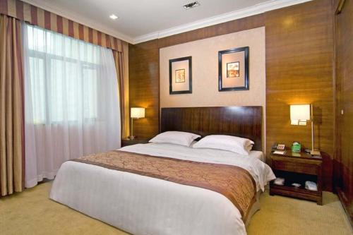 A bed or beds in a room at Jianguo Hotspring Hotel