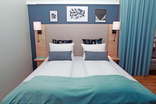 A bed or beds in a room at Quality Hotel Grand Steinkjer