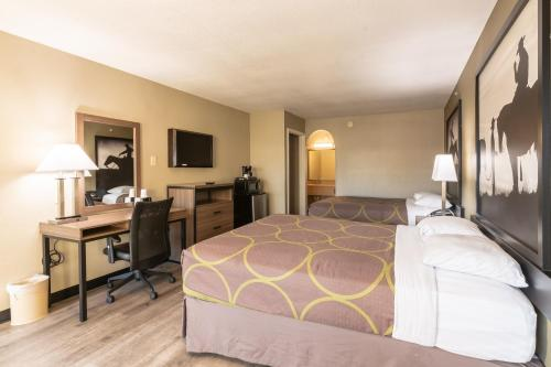 A bed or beds in a room at Super 8 by Wyndham Dallas East