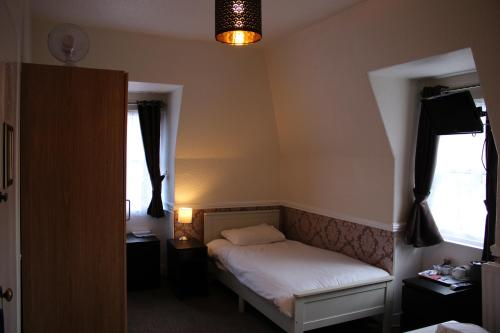 A bed or beds in a room at Ardmillan Hotel