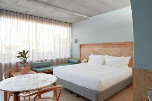 A bed or beds in a room at The Calile Hotel