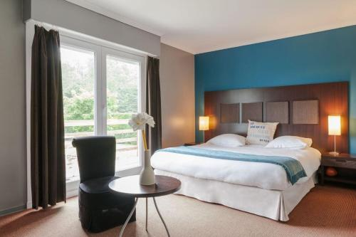 A bed or beds in a room at Les Jardins d'Ulysse, The Originals Relais (Relais du Silence)