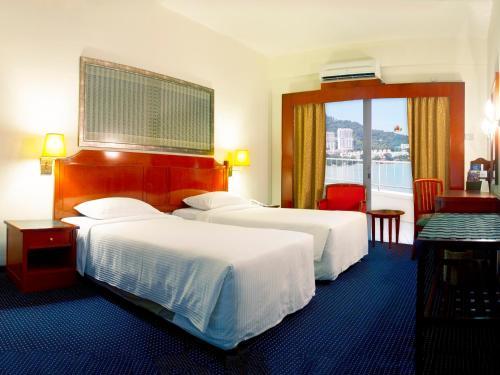 Een bed of bedden in een kamer bij Rainbow Paradise Beach Resort