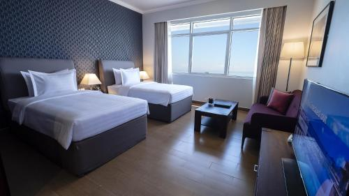 A bed or beds in a room at The Curve Hotel
