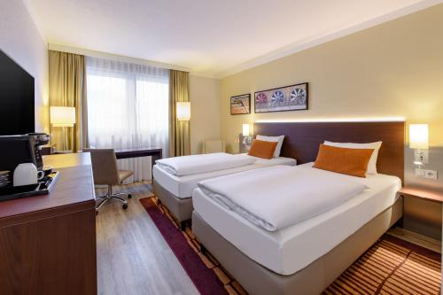 A bed or beds in a room at Mercure Hotel Duisburg City