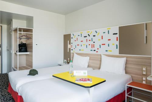 A bed or beds in a room at ibis Styles Guyancourt Versailles