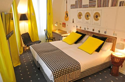 A bed or beds in a room at Hôtel du Triangle d'Or