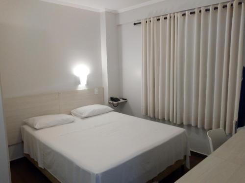 A bed or beds in a room at Hotel Zé Maria