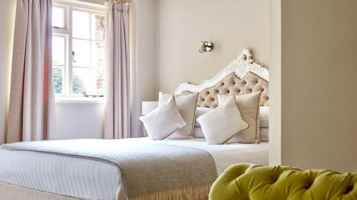 A bed or beds in a room at The Priory Hotel