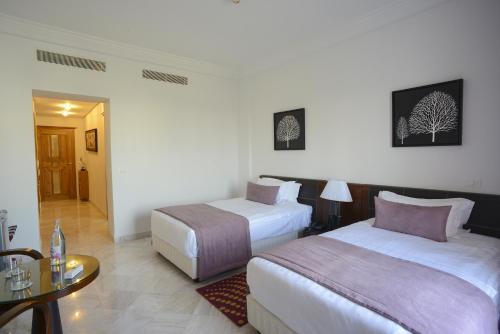 سرير أو أسرّة في غرفة في فندق ذا بنتهاوس سويتس
